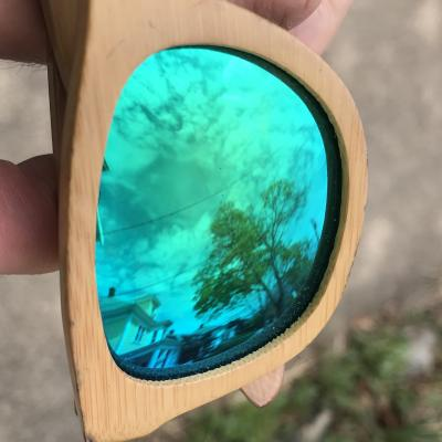 sunglasses with reflective lenses reflecting the sky, a tree, and a house