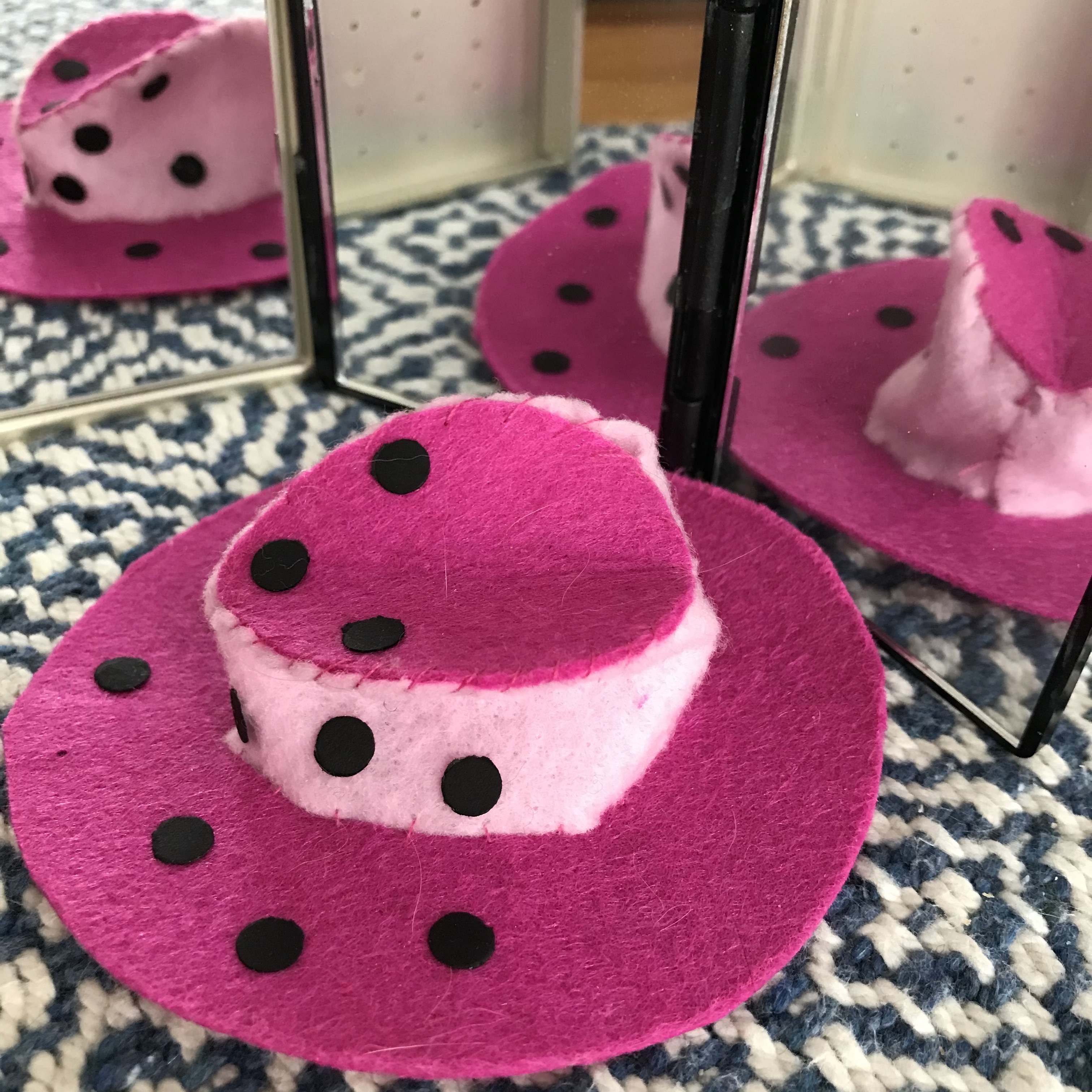 pink hat with polka dots reflected in multiple mirrors
